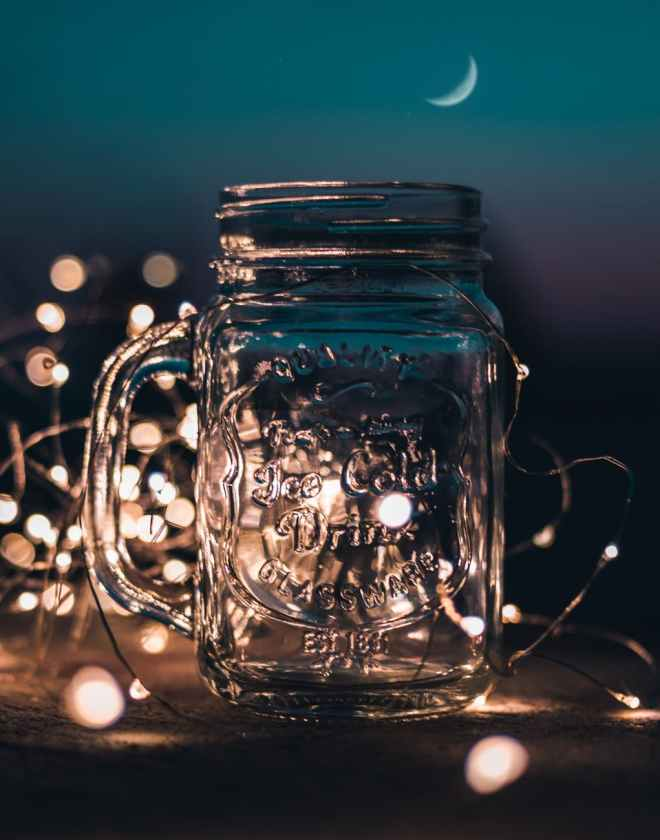 shallow focus photograph of clear glass mason jar with fairy lights